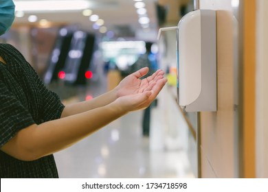 Hands under the automatic alcohol dispenser. Infection and hospitably concept. save and protect disease virus against germs and clean in the public area.