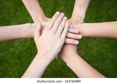 Hands uniting with grass background