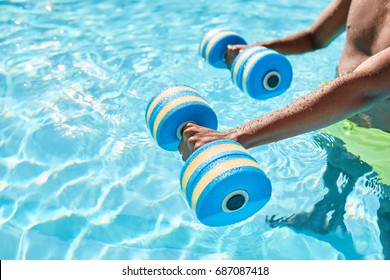 Hands of an unknown black guy holding dumbbells for aqua aerobics standing in the swimming pool on warm summer day