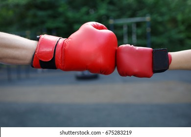 The hands of unknown men and child dressed in red boxing gloves touch each other in a summer park on the street