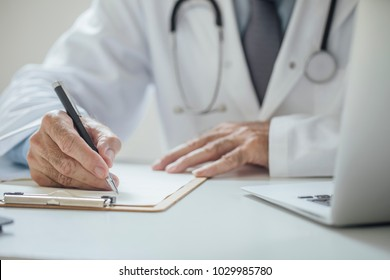 Hands of unrecognisable doctor sitting at his office and writing drug prescription.