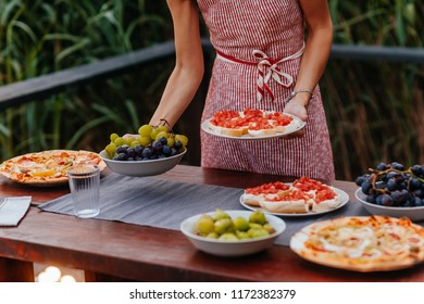 Hands of unrecognisable woman holding a plate with food for outdoor dinner party.