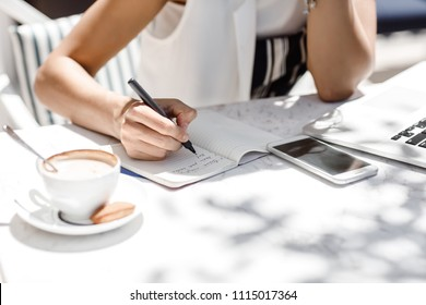 Hands of unrecognisable woman sitting at coffee shop and writing in her notebook.