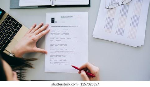 Hands of unrecognisable woman teacher grading high school exam.