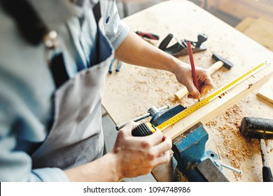 Hands of unrecognizable craftsman using measuring tape and pencil to make marks on piece of wood placed in workbench vice, high angle view