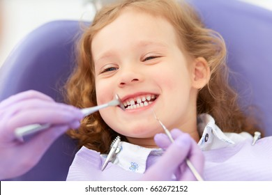 Hands of unrecognizable pediatric dentist making examination procedure for smiling cute little girl sitting on chair in hospital. Dentist office. Little girl sitting in the dentists office