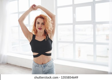 With hands up. Attractive redhead woman posing in the spacey room near the window.