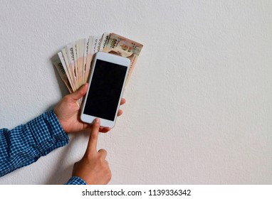Hands use mobile phone with pile of Thai Baht money in concrete wall