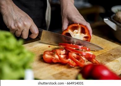 Hands using a knife chopping bell pepper