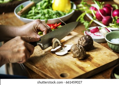 Hands using a knife chopping mushroom