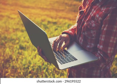 Hands using laptop and typing outside on nature background