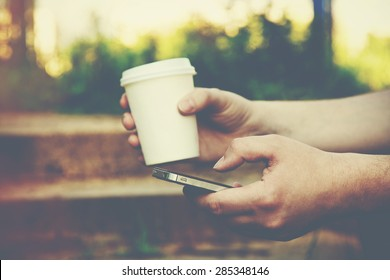 hands using a phone texting on smartphone app and holding paper cup of coffee