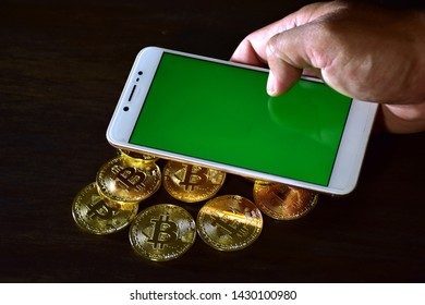 Hands are using smart phones to digital on-line (green screen) and there is a pile of coins placed on the side of the bitcoin.