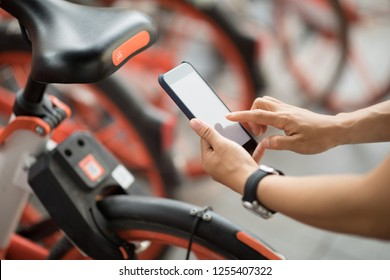 Hands using smartphone scanning the QR code of shared bike in city