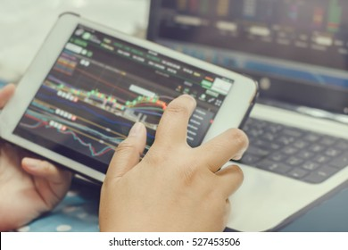 hands using tablet with stock chart market on screen and computer laptop with stock chart on background : business and technology concept