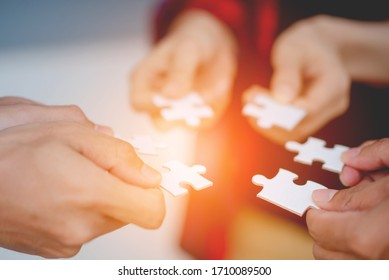 The hands of a variety of people including the Asian jigsaw puzzle And gather parts to find suitable partners to support teamwork to find common problem solving concepts, close-up perspectives