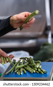 The hands of a vendor at a farmers market placing asparagus on a scale to measure an amount to sell to a customer.