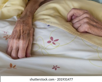 The hands of a very old and skinny woman in bed