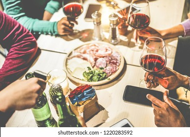 Hands view of friends group drinking wine inside vintage pub restaurant - Young people eating appetizer food and having fun together - Youth and dinner concept - Focus on right bottom hand fingers