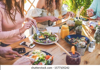 Hands view of young people eating brunch and drinking smoothies bowl with ecological straws in trendy bar restaurant - Healthy lifestyle, food trends concept - Focus on left woman hand, dish