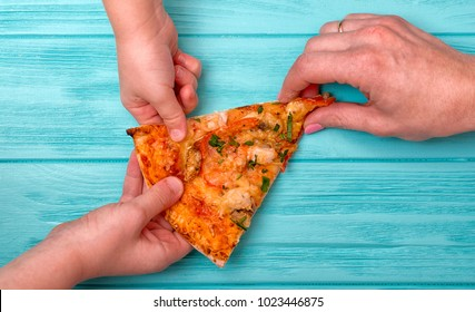 Hands want to take the last piece of pizza from the table.