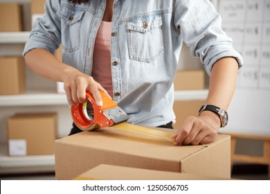 Hands of warehouse worker applying adhesive tape on cardboard box