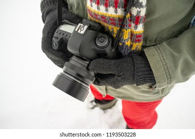 Hands in warm knitted gloves hold a professional camera, in the cold winter against the snow. Close-up.