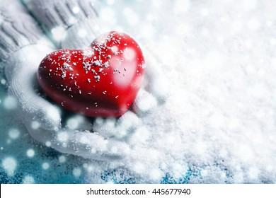 Hands in warm white gloves holding red heart on snowy background. Snow effect