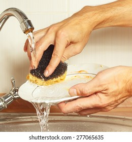Hands wash the dirty plate under running water in the kitchen
