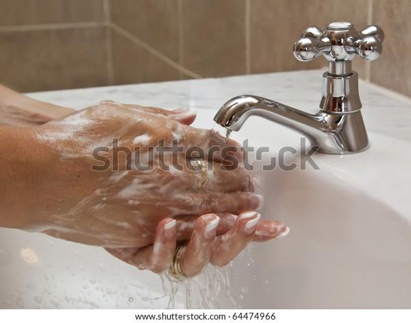 Hands washing in basin