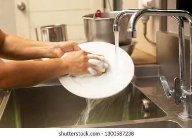 Hands washing dirty dishes with running water in kitchen sink.