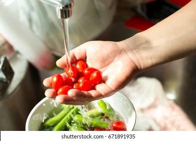 Hands washing fresh cherry tomatoes in running water in kitchen sink