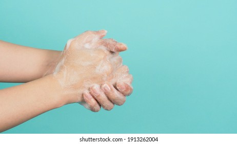 Hands washing gesture with foaming hand soap on green and Tiffany Blue  background.