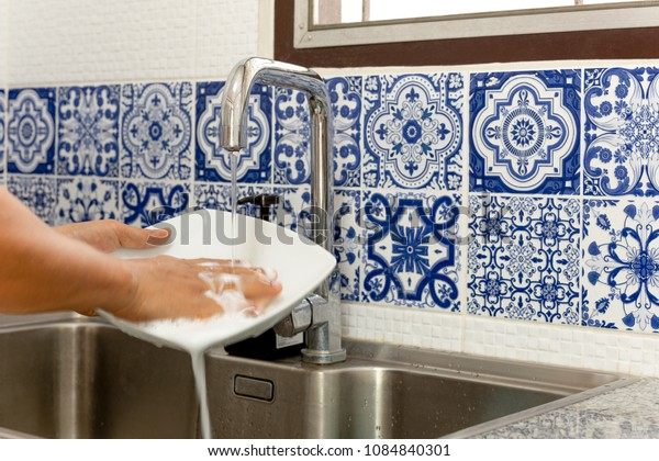 Hands washing white plate in kitchen sink with running water with blue tile