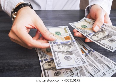 Hands with watch counting dollar bank notes on dark wooden table