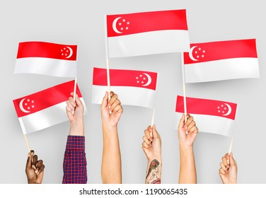 Hands waving flags of Singapore
