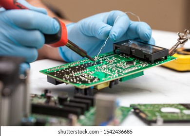 Hands wearing gloves solders and verifies computer circuit board using soldering iron and multimeter