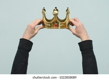 Hands are wearing a golden crown on head copy space isolated on light blue background. Winner. Leader. Selfish person. Award ceremony concept.