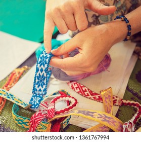 Hands weave belt in the Slavic style, the process of weaving a belt of cotton threads.