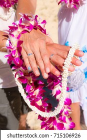 Hands of a wedding couple joined with floral and wedding lei