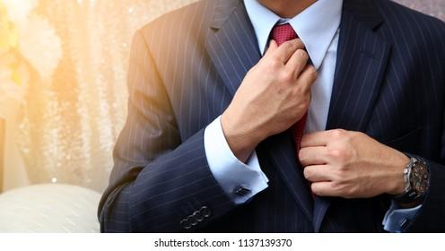Hands of wedding groom fixing the tie prepares for wedding