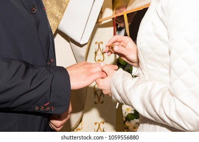 Hands of a wedding heterosexual couple. Bride putting a wedding ring on groom's finger