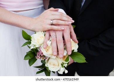Hands with wedding rings and flower bouquet