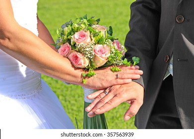Hands with wedding rings and flowers in summer on the grass