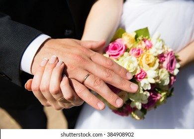 Hands with wedding rings on bridal bouquet