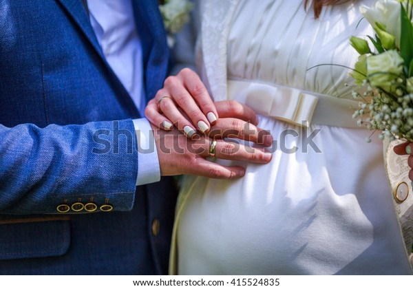 Hands with wedding rings on pregnant bride