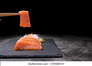 The hands were holding the chopsticks to hold the salmon sashimi, which was arranged on a black stone plate on a old table, with copy space.