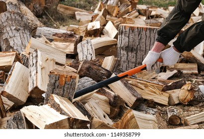 Hands in white gloves with a cleaver, firewood is stuck, firewood is flying off a cleaver in the wood