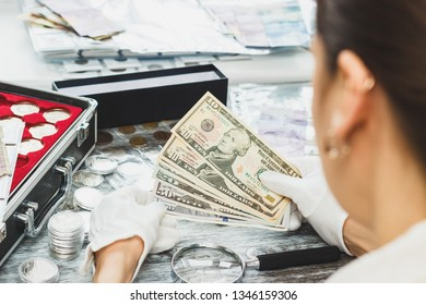 Hands in white gloves, different American dollars, numismatics concept, blurred background