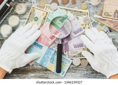 Hands in white gloves, different American dollars and Indonesian rupiahs, numismatics concept, blurred background